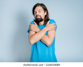 man with a beard embraces himself, cozy, isolated studio photo on a background