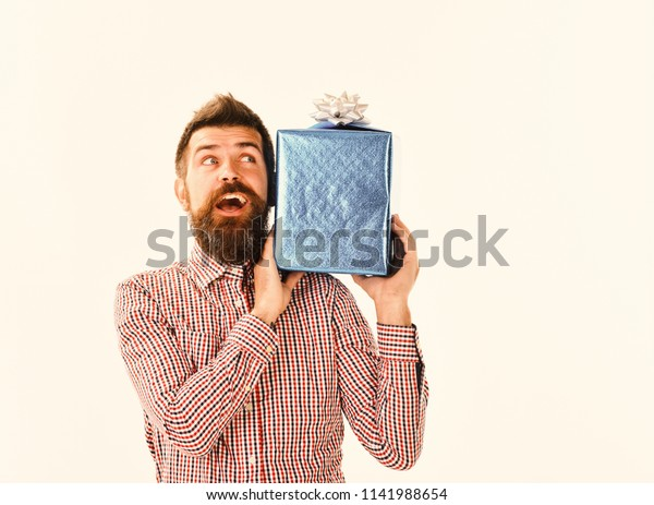 Man with beard and excited face isolated on white background. Macho with wrapped blue gift and white bow. Surprise and holiday gift concept. Guy in plaid shirt holds present box on shoulder.
