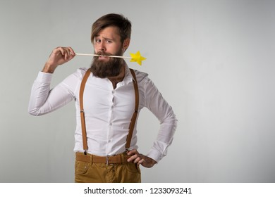 A man with a beard fooling around with a children's magic wand on a gray background