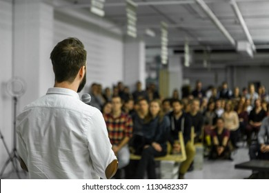 Man with beard gives a public speech in front of 200 people, in an industrial environment