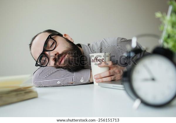Un homme à barbe dans des lunettes dort au bureau sur une table sur un ordinateur portable avec du café à la main