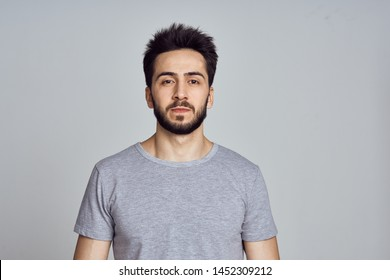 man with a beard in a gray t-shirt