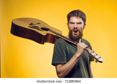 man with a beard guitarist holding a guitar on his shoulder singing songs on a yellow background, music, chords, rock