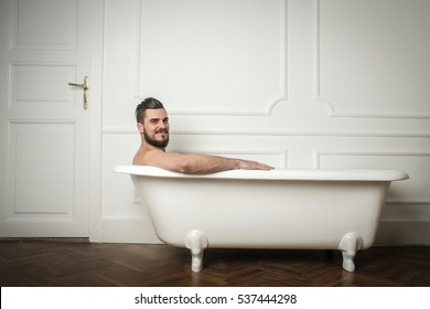 Man with beard having a bath in a white buthtub