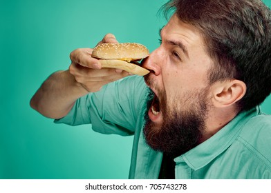 a man with a beard is holding a cheeseburger's nose on a green background, fast food