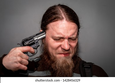 A man with a beard holding a gun at his temple. The concept of suicide.