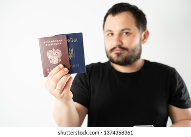 A man with a beard holding a passport of Russia and Ukraine translation: - Ukraine. Passport, Russian Federation