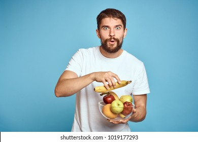 man with a beard holding a plate of fruit on a blue background