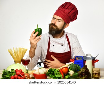 Man with beard holds bell pepper on white background. Cook with curious face in burgundy uniform sits by kitchen table with vegetables and kitchenware. Restaurant cuisine concept. Chef prepares meal