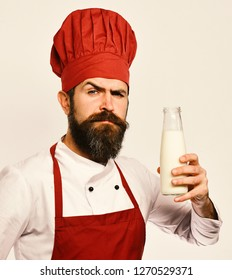 Man with beard holds bottle of milk on white background. Homemade food concept. Cook with confident face in burgundy uniform has liter of fresh milk. Chef with milkshake or yoghurt.