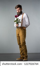A man with a beard holds with a bouquet of roses in his hand