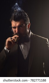 Man with beard holds cigar on grey background. Businessman with confident face smokes cuban cigar. Business and bad habit concept. Guy in classic suit has five minute break for smoke.