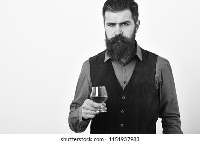 Man with beard holds glass with alcohol on white background, copy space. Alcohol luxury drink concept. Barman in elegant uniform with serious face serves cognac. Waiter with whiskey or scotch in hand.