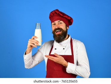 Man with beard holds glass bottle on blue background. Cook with happy face in burgundy hat and apron presents milk. Dairy products and cooking concept. Chef with milkshake or yoghurt.
