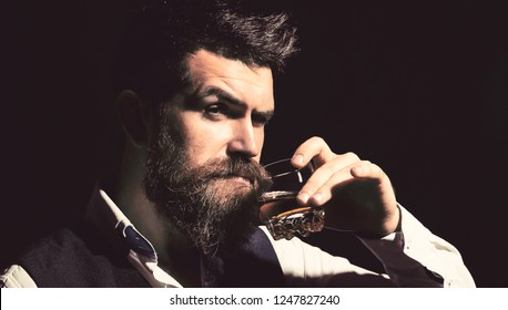 Man with beard holds glass brandy. Bearded drink cognac. Sommelier tastes drink. Man holding a glass of whisky. Sipping whiskey. Portrait of man with thick beard. Macho drinking. Degustation, tasting.