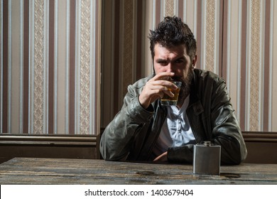 Man with beard holds glass brandy. Man holding a glass of whisky. Handsome stylish bearded man is drinking whiskey