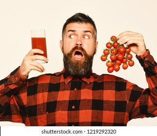 Man with beard holds glass of juice and vegetables isolated on white background. Guy holds homegrown harvest. Farming and autumn concept. Farmer with surprised face shows bunch of red cherry tomatoes