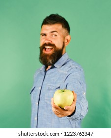 Man with beard holds green fruit isolated on green background, defocused. Guy presents homegrown harvest. Farmer with smiling face holds fresh apple, close up. Gardening and fall crops concept
