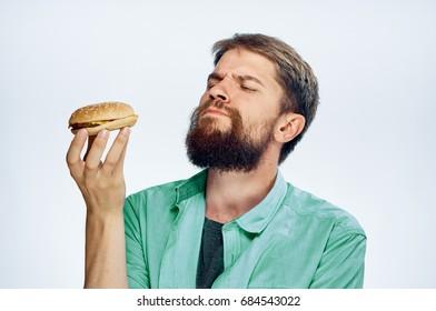 Man with a beard holds a hamburger on a light background