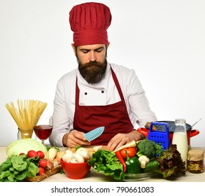 Man with beard holds knife on white background. Cook with serious face in burgundy uniform sits by kitchen table with vegetables, kitchenware and wine. Chef prepares meal. Cooking process concept