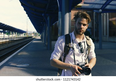 Man with beard holds photocamera on station background. Urban photo and travelling concept. Tourist ready to take picture of cityscape. Young traveller or photographer waits for train.