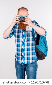 Man with beard holds photocamera on white background. Photography and tourism concept.