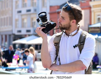 Man with beard holds photocamera on urban background. Tourist takes picture of cityscape. Young traveller or photographer with curious face goes sightseeing. Photography and tourism concept.