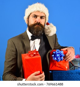 Man with beard holds presents. Xmas corporate party concept. Businessman with confident face and stack of boxes on blue background. Santa in retro suit presents blue and red gifts.