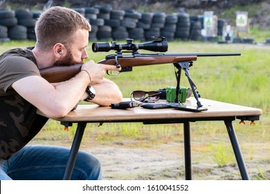A man with a beard holds a sniper rifle, checks and charges it in the forest, the concept of military conflict, military action.