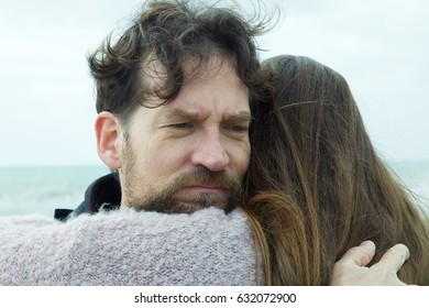 man with beard hugging woman sad