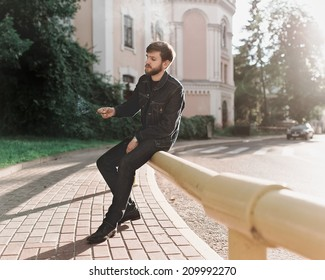 Man with beard in jute and jeans sitting beside the road with a cigarette and smokes