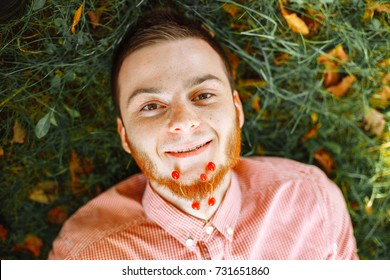 Man with beard lay at ground and smile.