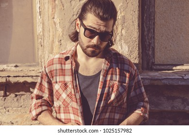 Man with beard and long hair posing in front of a ruined house.