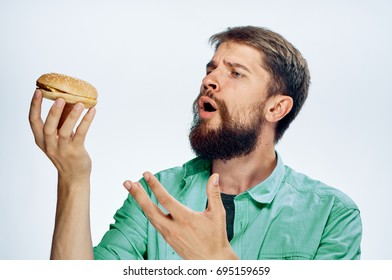 A man with a beard looks at a cheeseburger on a light background of fast food