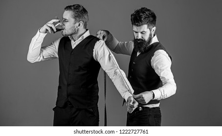 Man with beard and mustache busy with measuring. Client, businessman with arrogant face smoke cigar while tailor working. Tailoring and exclusive concept. Tailor measure client for sewing custom suit.