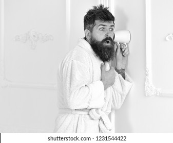 Man with beard and mustache eavesdrops using cup near wall. Hipster in bathrobe on surprised face secretly listen conversation. Privacy concept. Man in white interior spying, eavesdropping, copy space