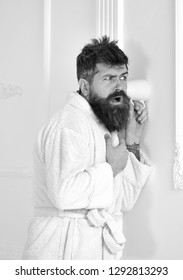 Man with beard and mustache eavesdrops using mug near wall. Hipster in bathrobe on concentrated face secretly listen conversation. Secret and spy concept. Man in white interior spying, eavesdropping.