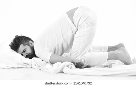 Man with beard and mustache fall asleep bending his knees, white background, copy space. Hipster with sleepy face lies on pillow, heavy sleeper. Heavy sleeper concept.