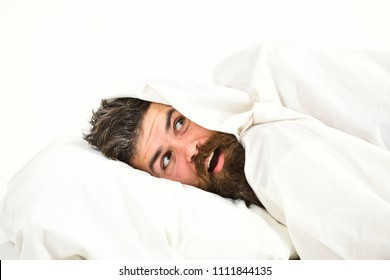 Man with beard and mustache hiding in bed under blanket at home. Guy with surprised face lay under white blanket.