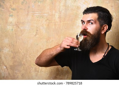 Man with beard and mustache holds alcoholic beverage on beige background, copy space. Service and restaurant drinks concept. Guy with glass of vodka in hand. Alcoholic with tricky face drinks spirits