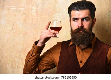 Man with beard and mustache holds alcoholic beverage on beige wall background. Macho with curious face drinks brandy or whiskey. Guy with glass of cognac. Service and tasting concept.