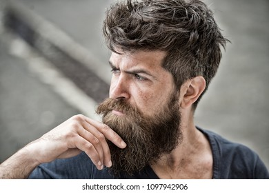 Man with beard and mustache looks thoughtful or troubled Bearded man on concentrated face touches beard. Hipster with beard looks thoughtful or troubled. Thoughtful mood concept