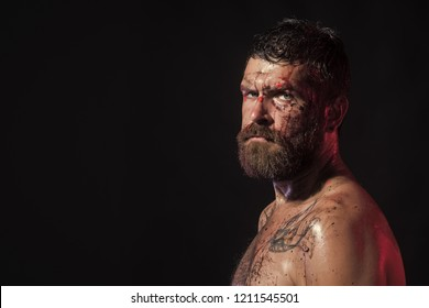 Man with beard, mustache on brutal bloody face. Bearded hipster with tattoo on chest on black background. Magic, enchantment, witchcraft. Wizard, sorcerer, warlock. Halloween, holidays, copy space