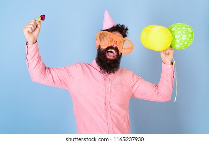 Man with beard and mustache on happy face holds air balloons, light blue background. Hipster in giant glasses celebrating birthday. Party concept. Guy in party hat with holiday attributes celebrates.