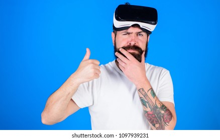 Man with beard and mustache with VR glasses, blue background. VR technology concept. Guy with VR glasses, head mounted display. Hipster on thoughtful face show thumbs up gesture