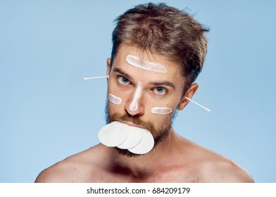 Man with a beard on a blue background, cosmetic cream, cotton pads.