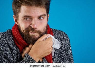 a man with a beard on a blue background holding a napkin, sick, illness, flu, runny nose.
