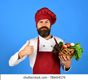 Man with beard on blue background. Cook with confident face in burgundy uniform holds vegetables in wicker bowl showing thumbs up. Vegetarian diet concept. Chef holds lettuce, tomato and mushrooms