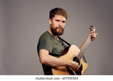 Man with a beard on a dark gray background holds a guitar, music, musician, musical instruments.