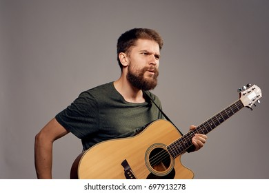 Man with a beard on a gray background holds a guitar, emotions.